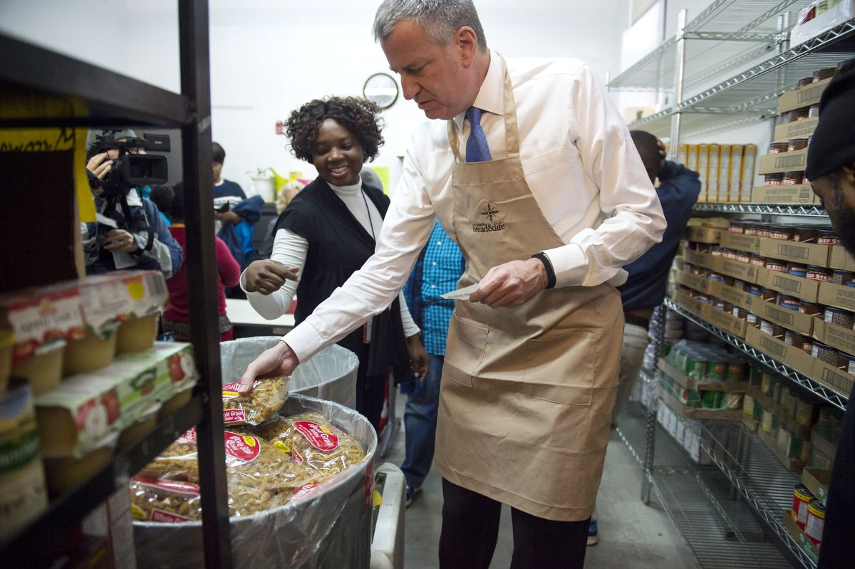 Mayor Bill de Blasio creates and delivers food packages with Joel Berg of NYC Coalition Against Hunger. St. John's Bread & Life, Brooklyn. Tuesday, November 24, 2015. Credit: Ed Reed/Mayoral Photography Office.