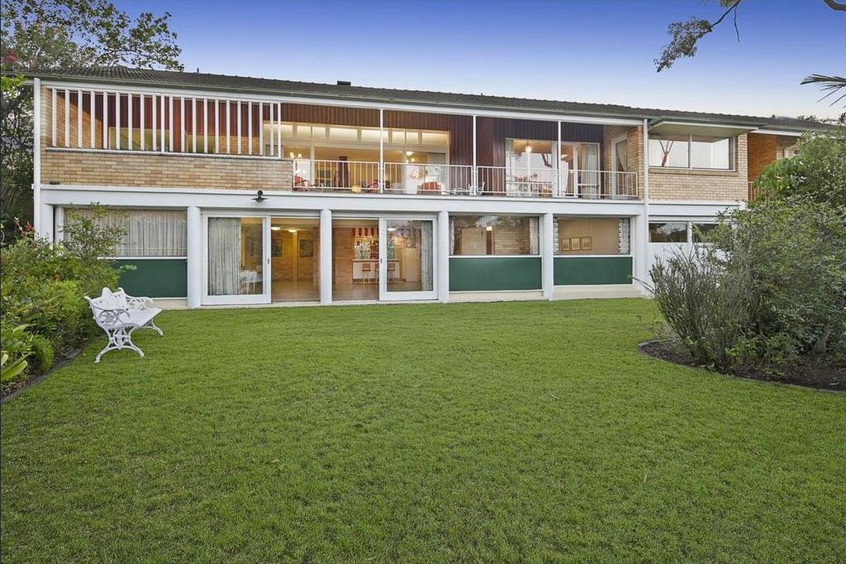 Exterior shot of back of the house with verandah on second floor and a large garden.