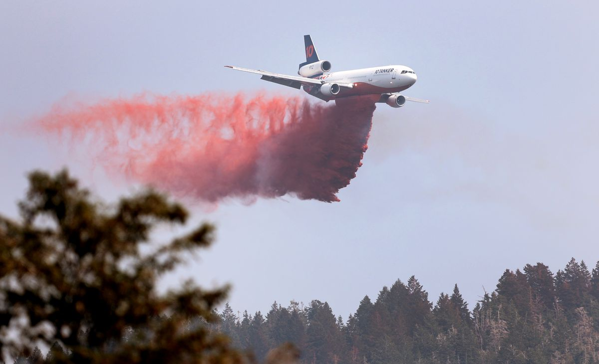 A large tanker begins a retardant drop as crews continue fighting the Parley's Canyon Fire near Park City on Sunday, Aug. 15, 2021.