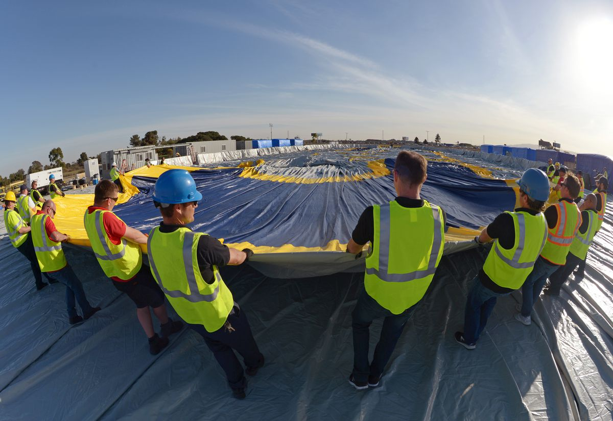 Workers flatten out the hangar material