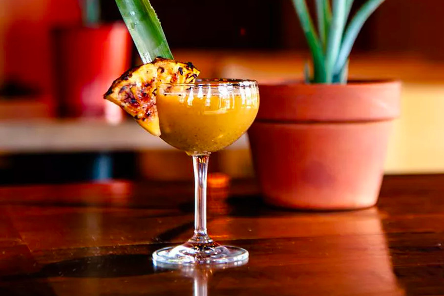 A yellow cocktail in a coup with grilled pineapple garnish.
