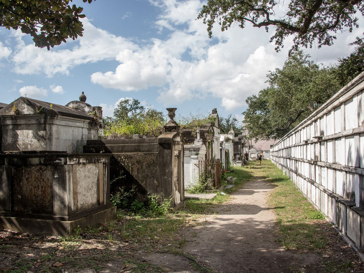 A New Orleans cemetery with above ground tombs and a path leading through the tombs.
