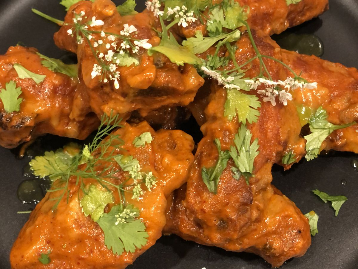 A pile of hot wings topped with cilantro sits on a black plate.