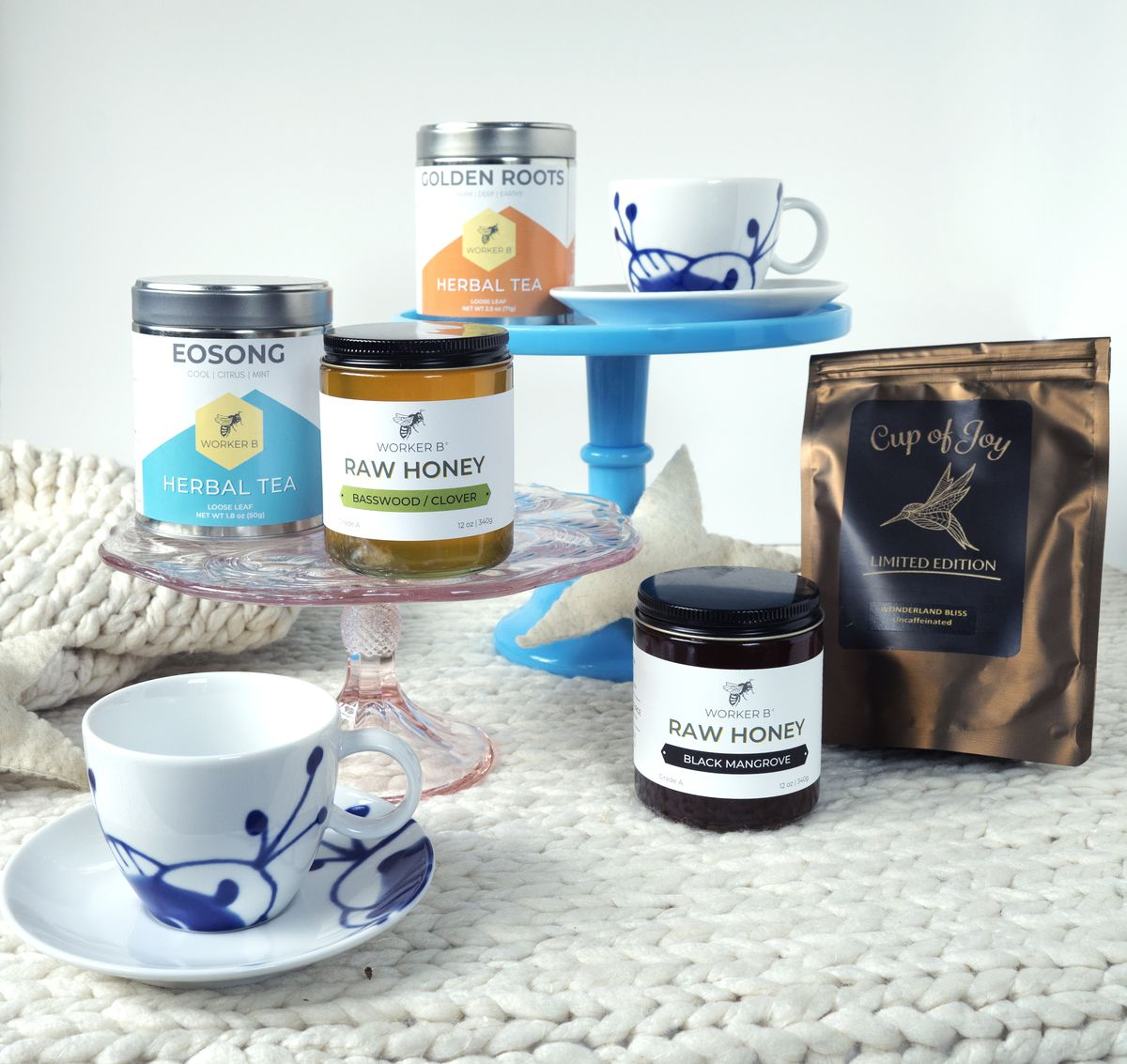 """On a white background, cakes stands hold tea and honey form Plan B, a dark shimmery bag contains another tea called """"Cup of Joy"""" and two tea cups are white with cobalt blue designs"""