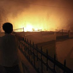 A woman watches the fire approaching a house in Ribeira do Farrio, near Ourem, Portugal, Monday, Sept. 3, 2012. A Portuguese official says authorities have asked other European countries to send help as the country's firefighters struggle to contain forest blazes being fueled by high temperatures and strong winds.