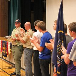 Scout leaders and members of Nate Christensen's scout troop applaud him at his final court of honor. He completed 132 merit badges in the Boy Scouts of America scouting program. He also happens to be autistic.