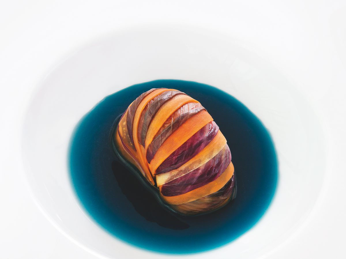 A hunk of vibrant lobster tail sits in a deep dark blue sauce in a white soup bowl that's nearly invisible against a neutral background