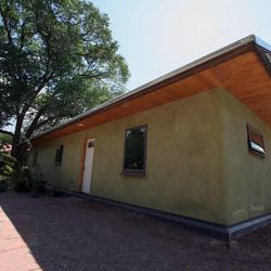 The homes built by Community Rebuilds take advantage of passive solar heating and also use donated and recycled materials. The dirt used to make the earthen plaster on the walls of the nonprofit organization's third home, pictured here, came from the hole that was dug for the home's foundation.
