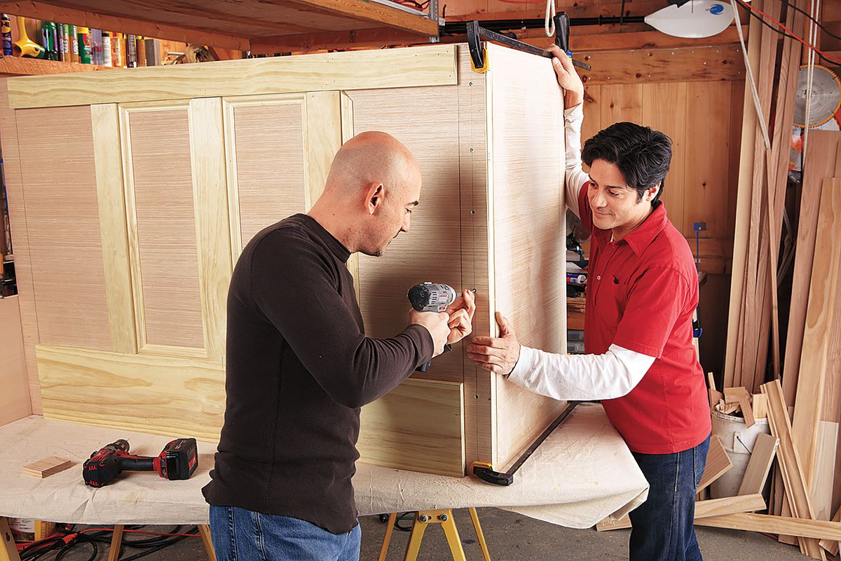 Men Nailing Walls To Side Panel's Framing Of DIY Bar