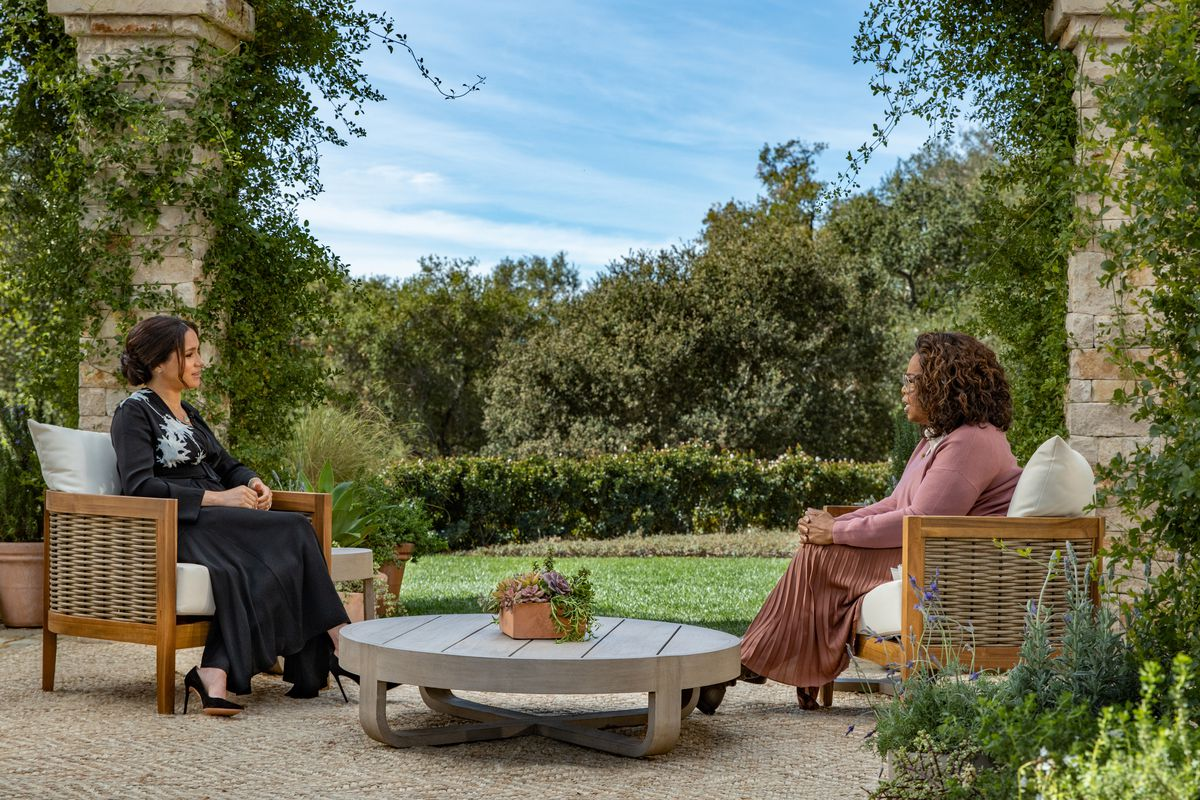 Meghan and Oprah sit outside to discuss Meghan's traumatic experiences under British tabloid scrutiny.