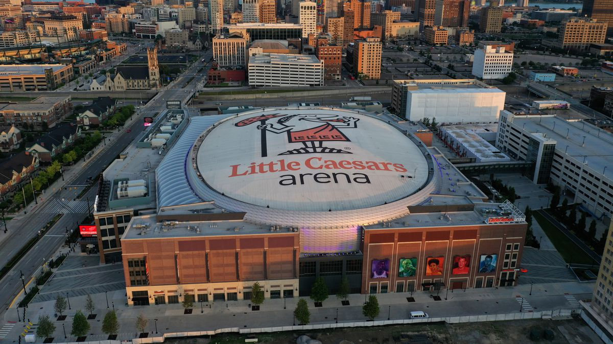 Aerial view of a huge arena with Little Caesars Arena on the dome. Many tall buildings are nearby.