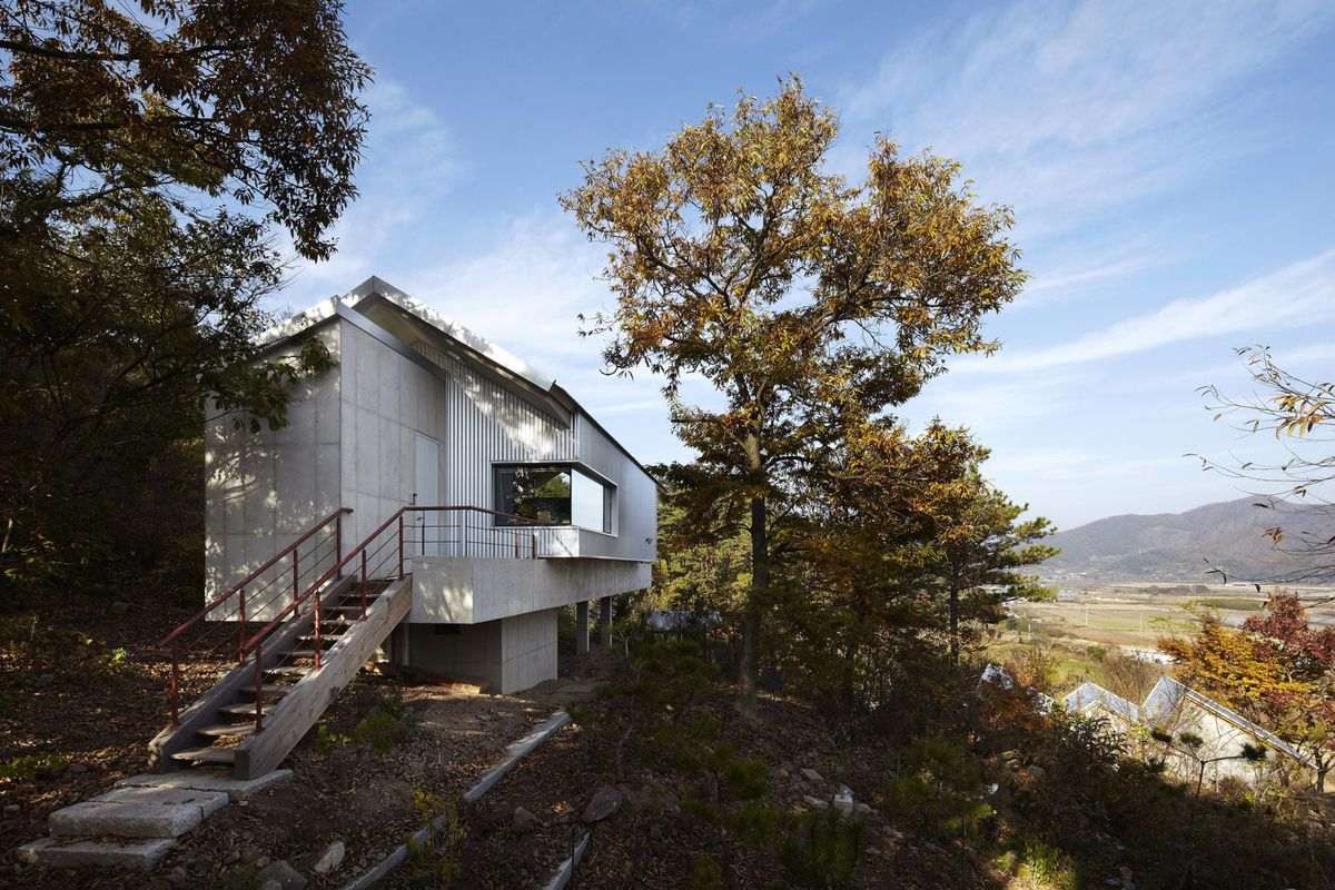 Simple gabled house with concrete walls, corrugated metal siding, deep roof overhangs, and a large deck sits ontop of a hill overlooking the countryside.