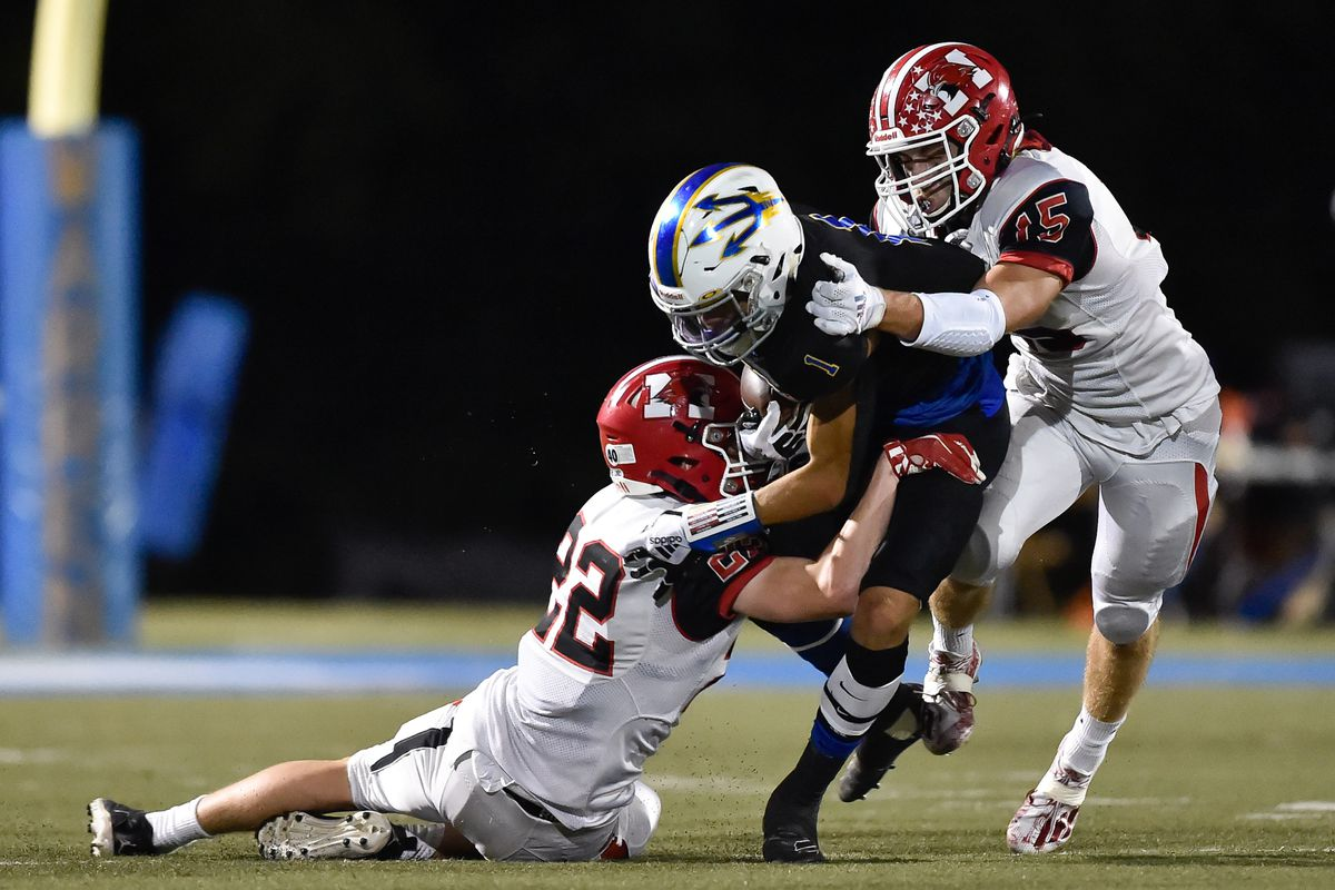 Maine South's Kevin Wolf (22) and Frank Bartell (15) stop Warren's Jailen Duffie (1).