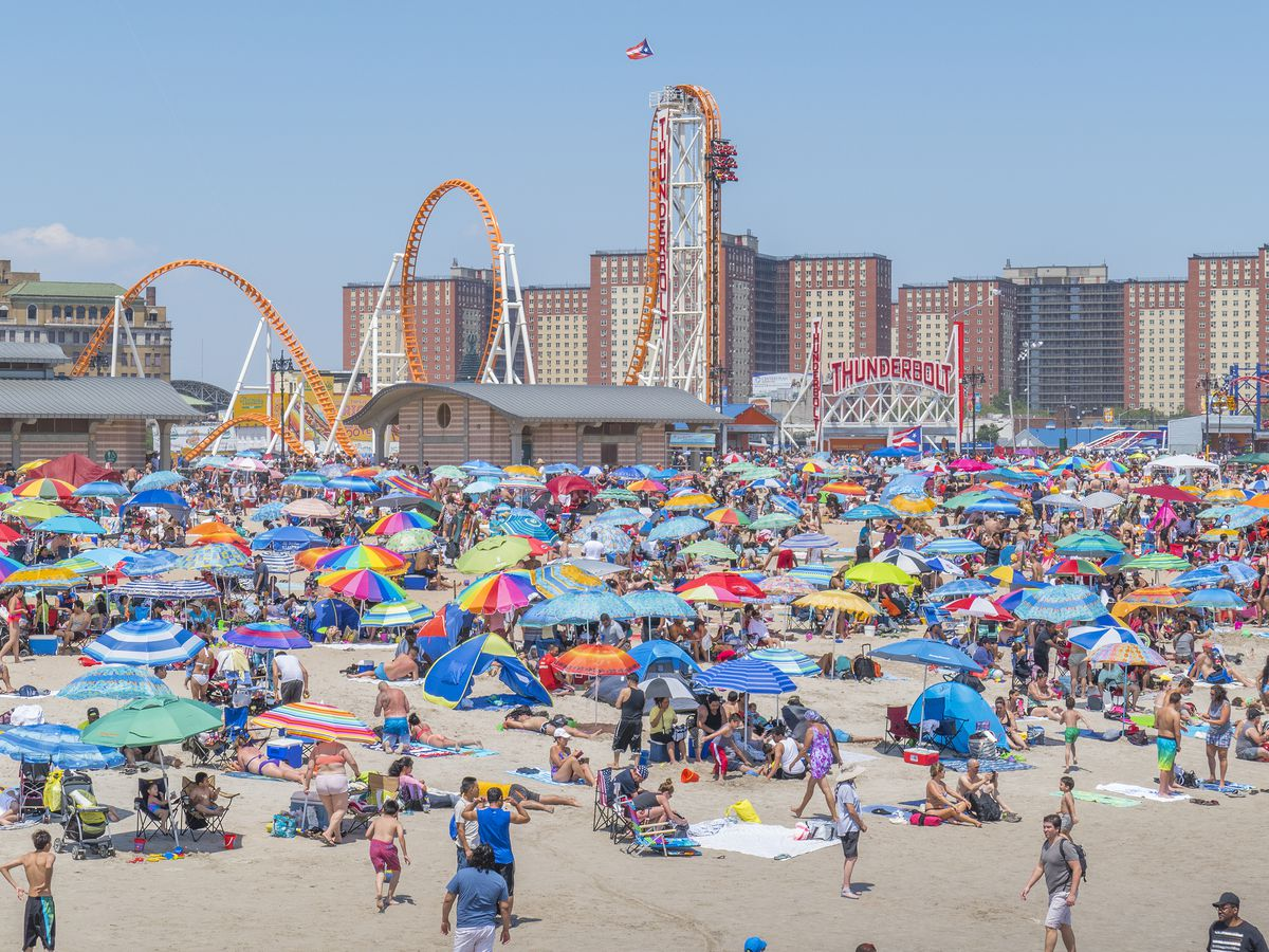 In the foreground is a beach with beachgoers, and colorful umbrellas. In the distance are amusement park rides and apartment buildings.