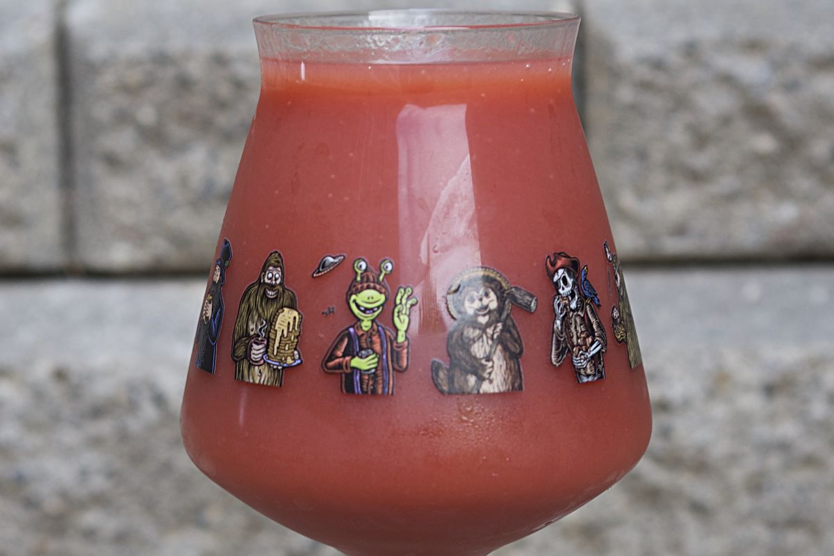 A thick strawberry-colored beer in a glass decorated with cartoon characters.