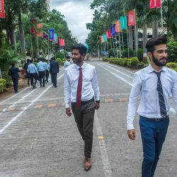 Tarun Marthano. left, and Kishan Demda walk after an interview  at the MIT World Peace University in Pune, Maharashtra, India, on August 15, 2017.