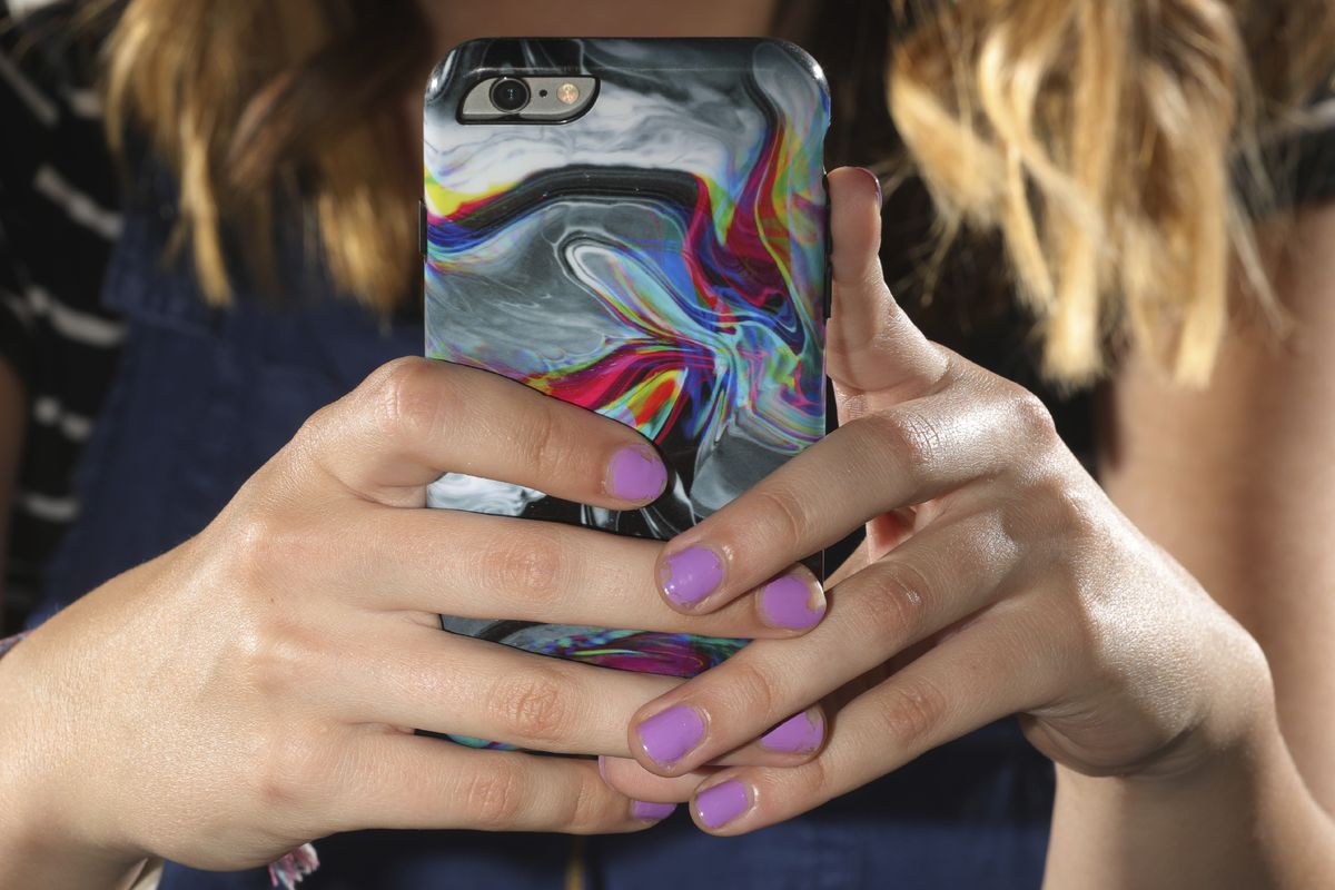 In this Monday, July 22, 2019, photo, Rachel Whalen looks at her phone at her home in Draper, Utah. Whalen remembers feeling gutted in high school when a former friend would mock her online postings, threaten to unfollow or unfriend her on social media an