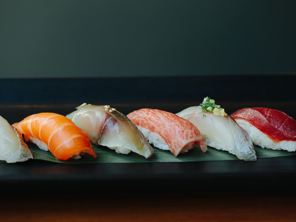A line of sushi laid out on a dark platter