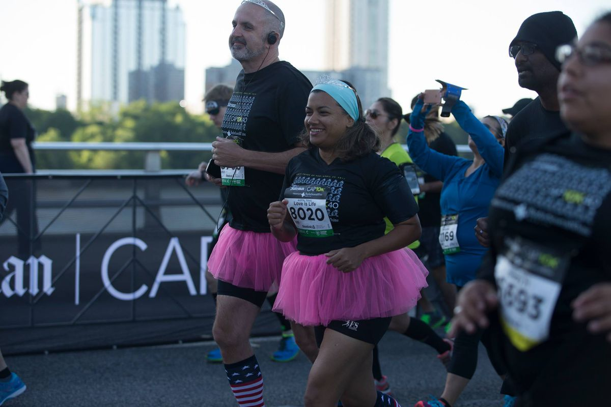 A man and a woman in pink tutus and black running clothes running on an Austin bridge with Lady Bird Lake and Downtown in background