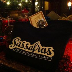 """<a href=""""http://sassafrasbar.com/"""">Sassafras Bar</a> is an awesome place to grab holiday libations and modified traditional Philly foods (e.g. a Philly cheesesteak with brie). Grab a gift certificate (varying amounts) at their Old City location and treat"""