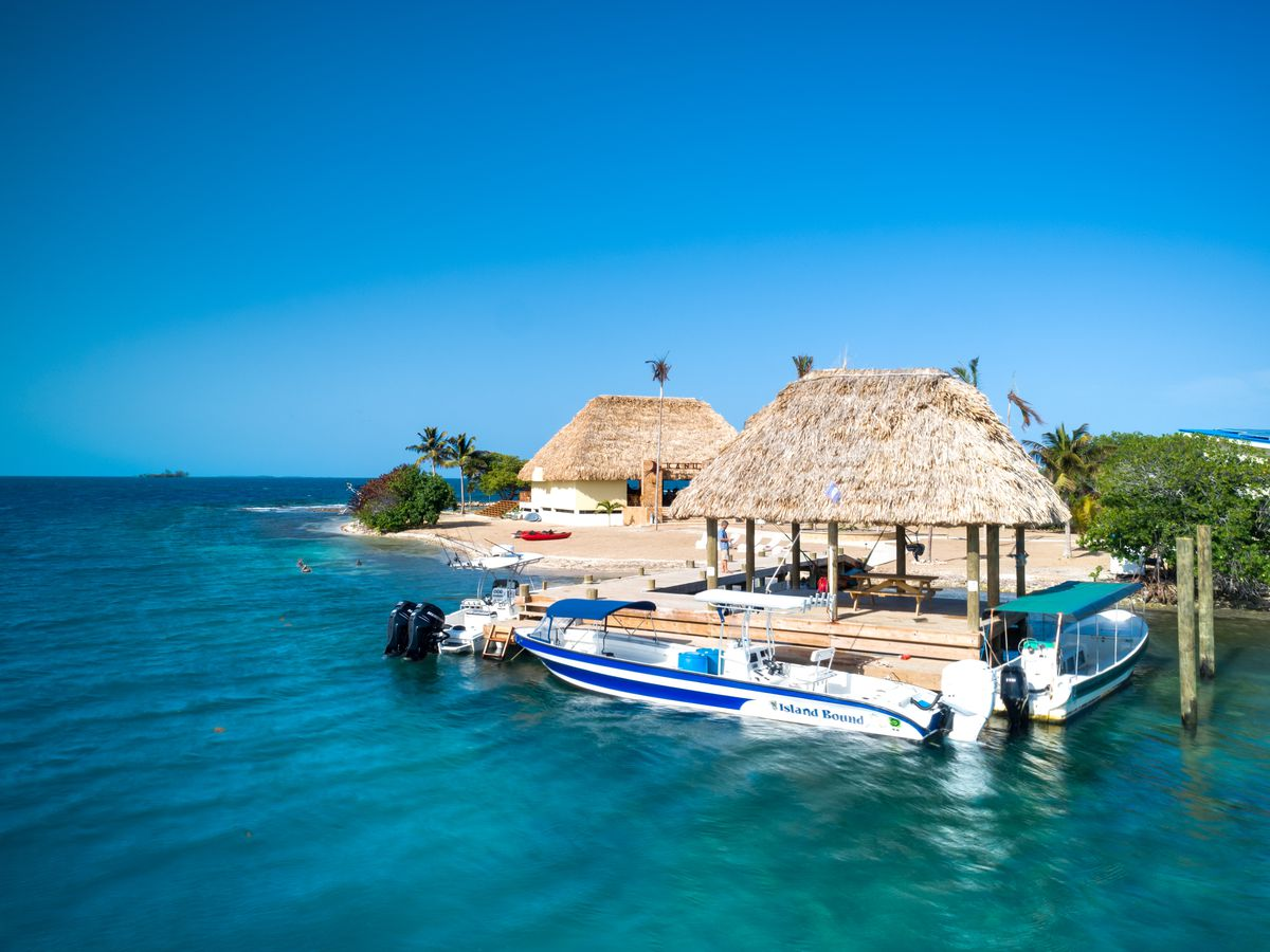 Two thatched roof structures on a private island in Belize. Two small boats are docked nearby.