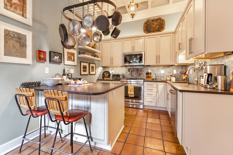 Folksy kitchen with pots and pans hanging above a breakfast bar, tile backsplash, white cabinets