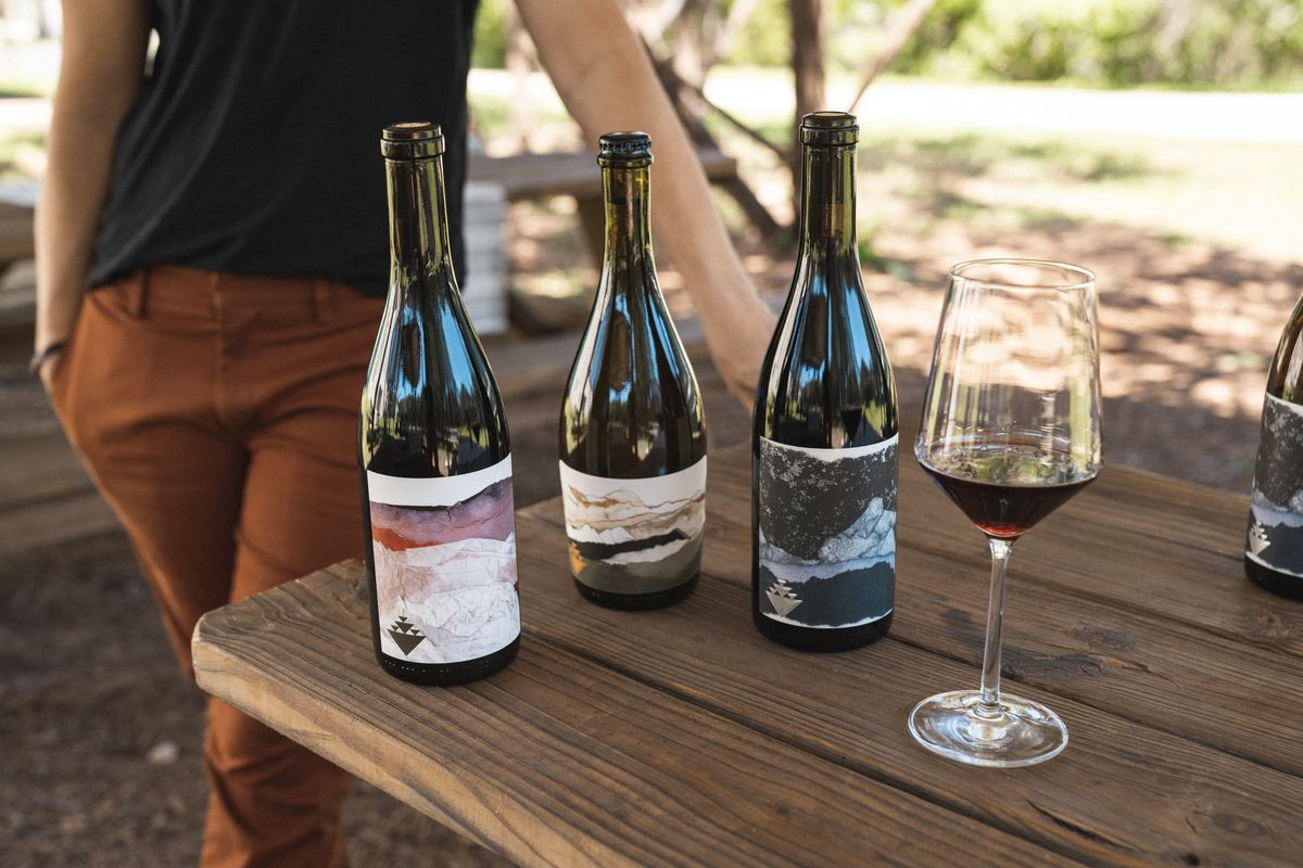 Three bottles of wine with abstract labels sit on an outdoor picnic table along with a glass of red wine; in the background Rae Wilson casually rests a hand on the table, her head cut off from the image.