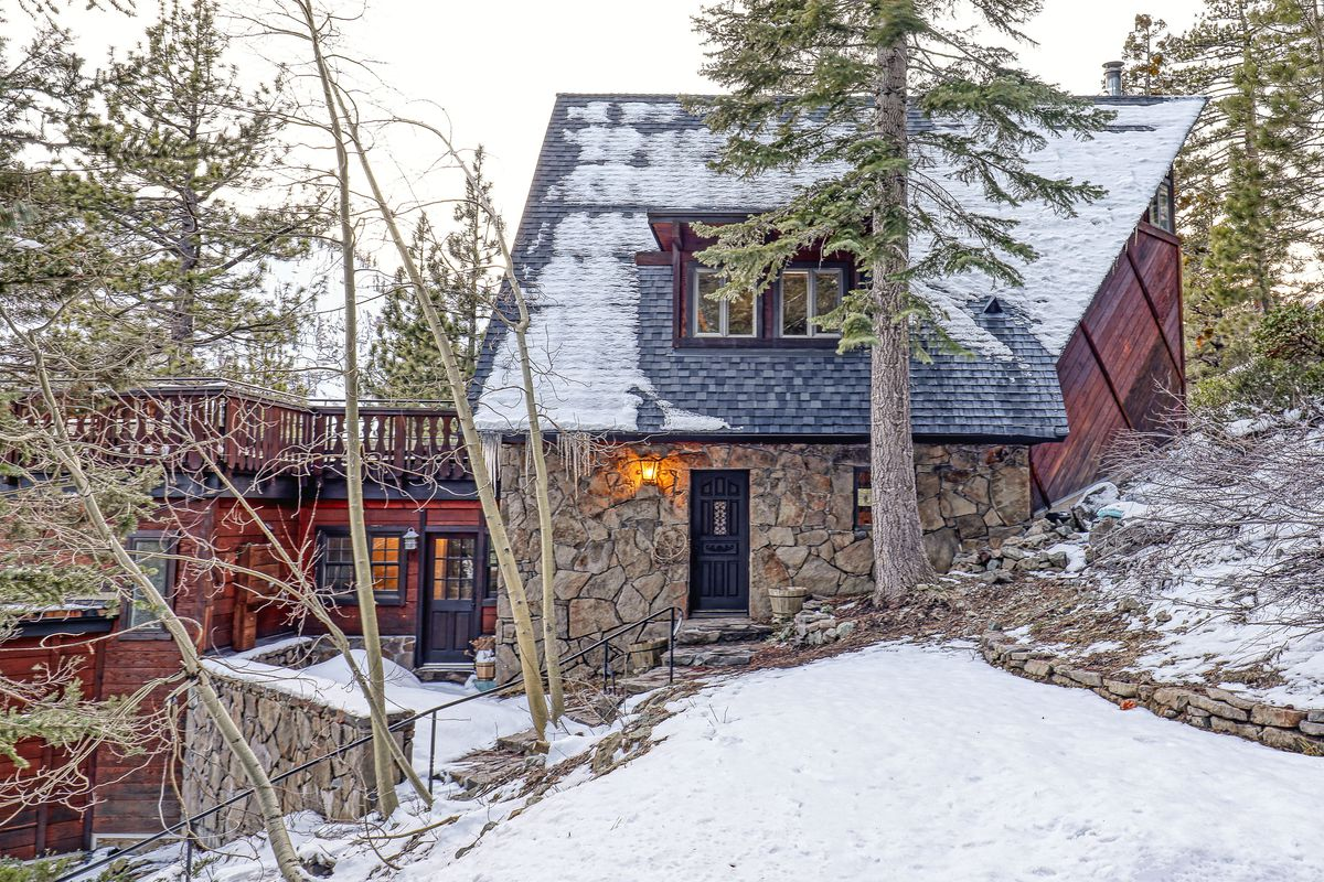 An exterior view of a ski house with exposed rock surrounded by snow and pine trees.
