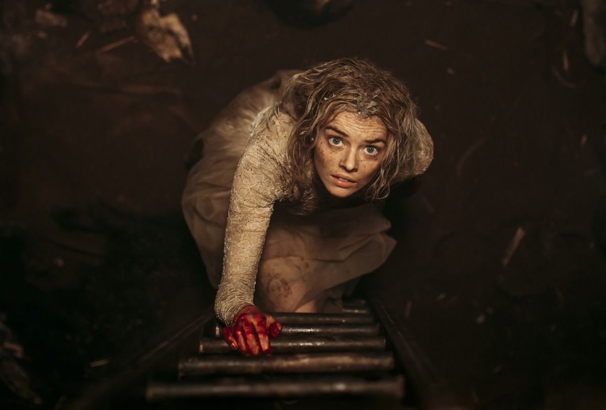 Grace (Samara Weaving) looks up a ladder, holding the first rung with her bloody hand in a shot from Ready or Not