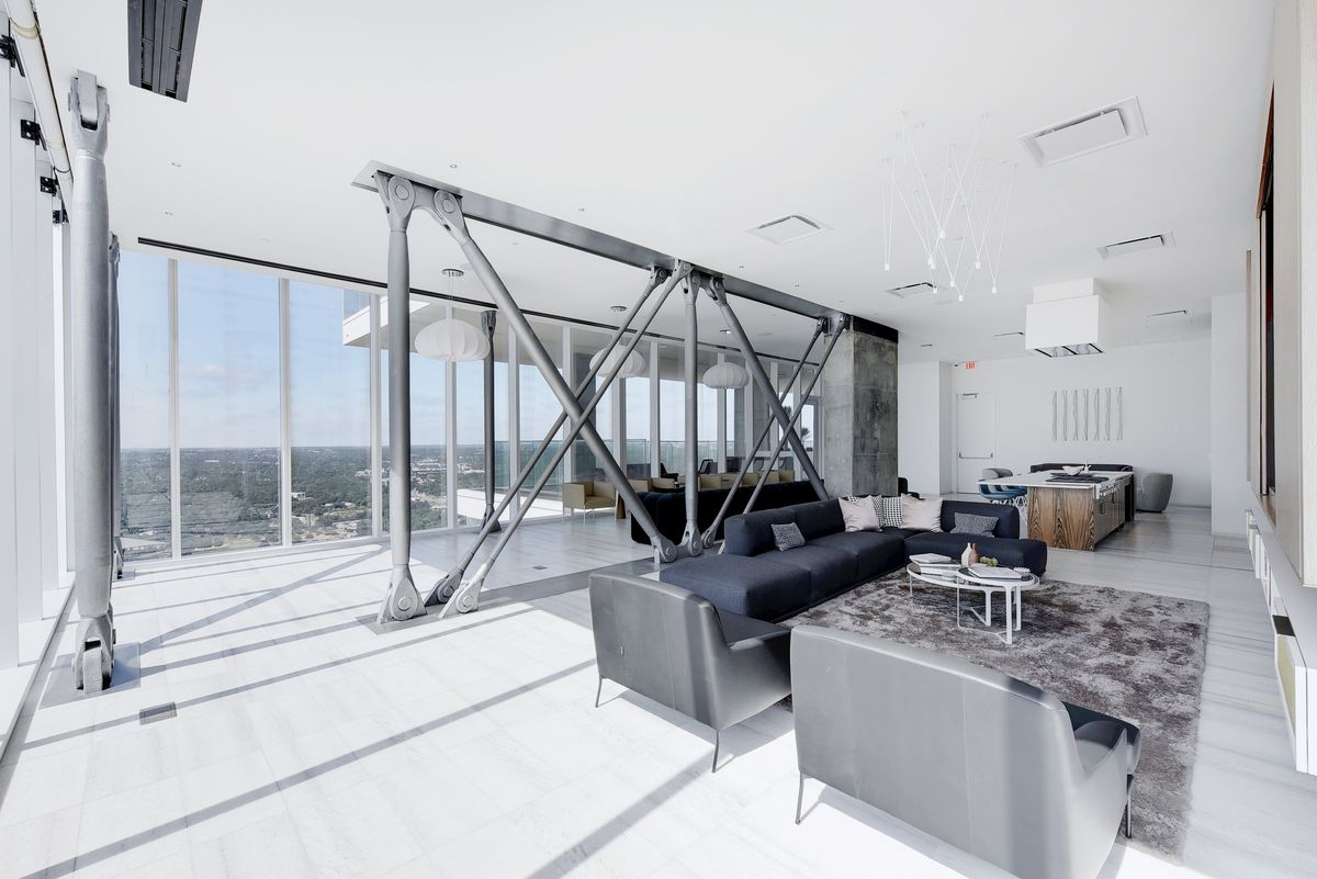 Large white room with industrial steel divider, two walls of windows with views of the horizon, and gray and dark furniture arranged around a rug.