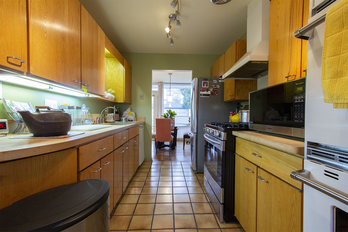 Two sets of wood cabinets in either side of a narrow kitchen.