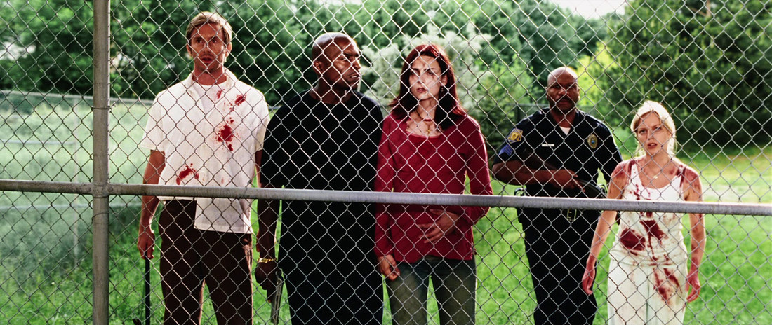The bloodied cast of Zack Snyder's Dawn of the Dead stands behind a chain-link fence