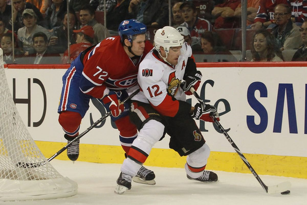 MONTREAL QC - SEPTEMBER 24: Mike Fisher #12 of the Ottawa Senators moves the puck around Mathieu Carle #72 of the Montreal Canadiens at the Bell Centre on September 24 2010 in Montreal Canada.  (Photo by Bruce Bennett/Getty Images)