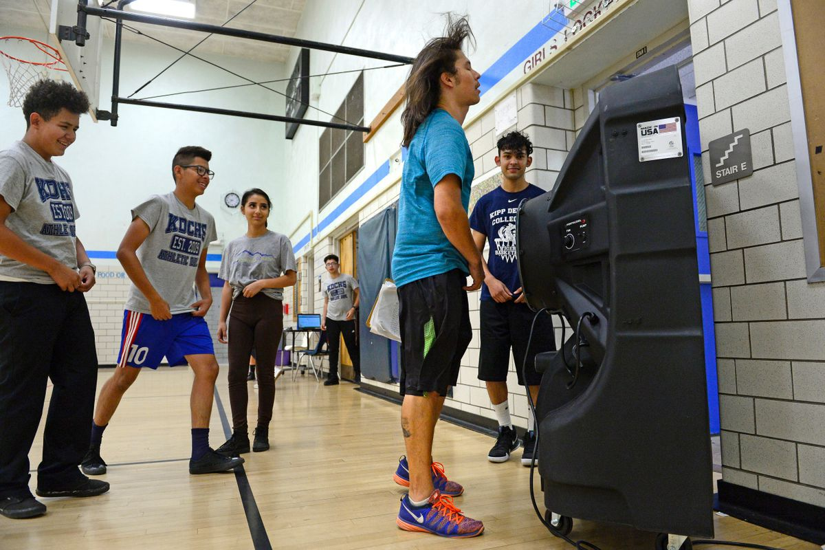 Students and a teacher in a gym stand around a portable air conditioning system. The air blows back the teacher's hair.