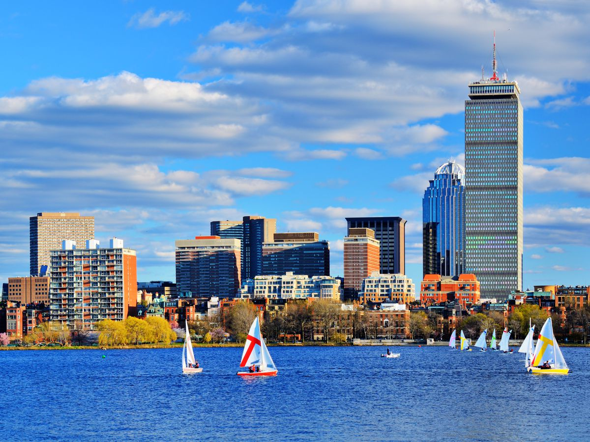 In the foreground is a body of water with sailboats. In the background is a city skyline with buildings of varying heights and architecture.