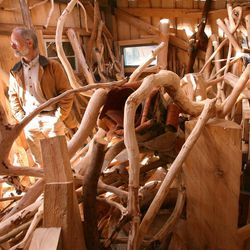 In this April 11, 2012 photo, local woodworking artist Phil Marshall looks out of a window in his drying shed at his studio outside of Fairbanks, Alaska, Marshall is the creator of distinctive, one-of-a-kind wooden furniture.