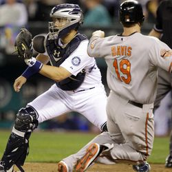 Baltimore Orioles' Chris Davis (19) scores in the fourth inning as Seattle Mariners catcher Jesus Montero waits for the throw during a baseball game, Wednesday, Sept. 19, 2012, in Seattle.