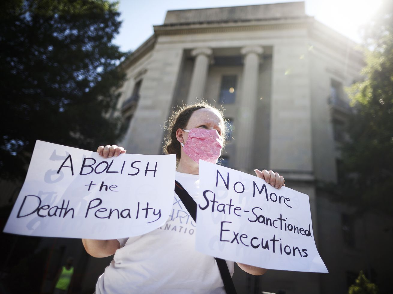"A person standing in front of the Justice Department building holds signs that read ""Abolish the death penalty"" and ""No more state-sanctioned executions."""