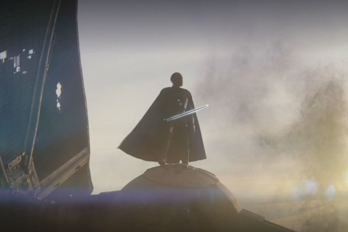 Moff Gideon stands atop his crashed TIE fighter, a dark blade silhouetted in white held in his right hand.