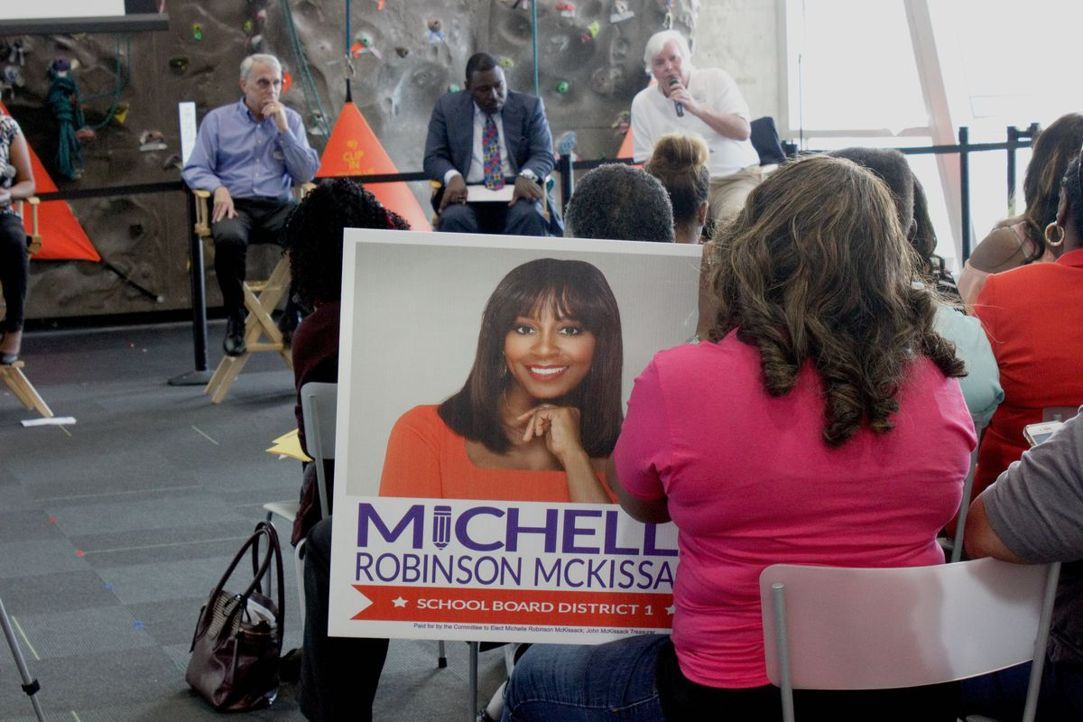 A supporter holds a sign for District 1 candidate Michelle Robinson McKissack at Chalkbeat's forum last Thursday.