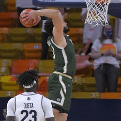Colorado State guard David Roddy goes up to dunk as Utah State center Neemias Queta (23) watches during the second half of an NCAA college basketball game Thursday, Jan. 21, 2021, in Logan, Utah.