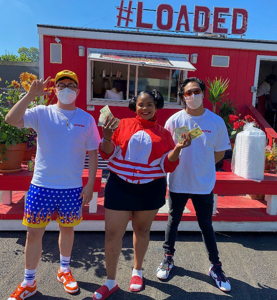 Kiauna Nelson — wearing in a red jacket and black shorts — stands outside a bright-red cart, shoulder-to-shoulder with two men. She's holding wads of dollars in her hands.