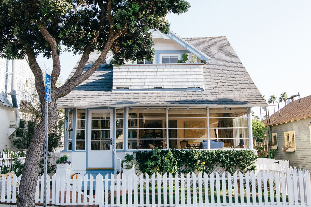 A little white home with blue trim and a screened-in front porch surrounded by a white picket fence.