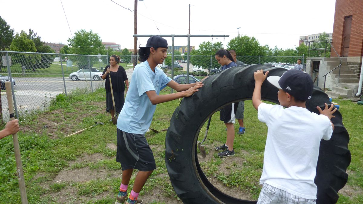 Elias Her Many Horses helps move an old tire out of the way as the campers work to expand their garden.
