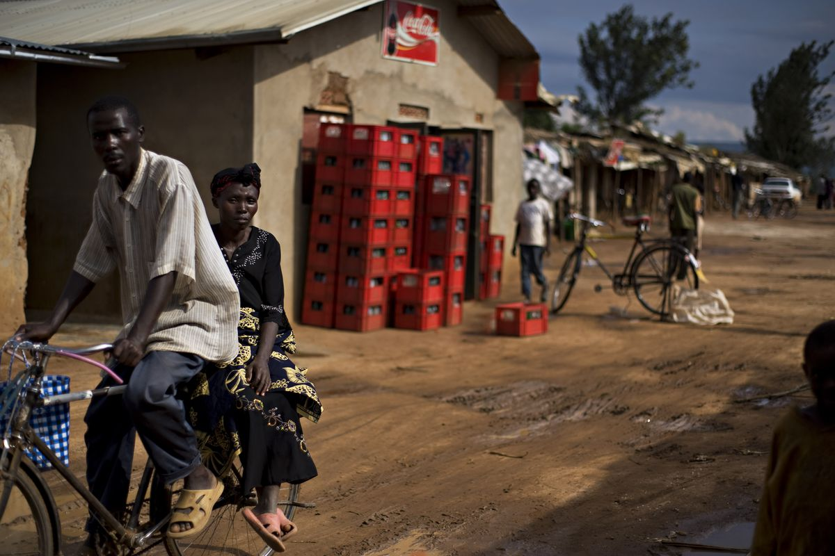 Rwandese refugees living in the Nakivale refugee camp in Uganda ride a bicycle in 2009.
