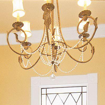 Golden vintage chandelier over a bathroom tub.