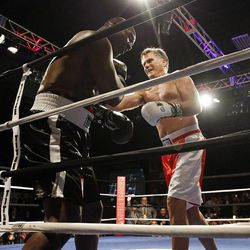 Former Massachusetts Gov. Mitt Romney, left, and Evander Holyfield fight during the Charity Vision Fight Night event in Salt Lake City, Friday, May 15, 2015.