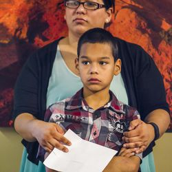 Eric Guadarrama, 10, stands with his mother, Grisel, after she speaks about her inability to afford health coverage for her family during a press conference at the state Capitol in Salt Lake City on Tuesday, Aug. 18, 2015.
