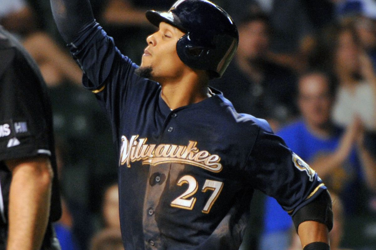 August 27, 2012; Chicago, IL, USA;  Milwaukee Brewers center fielder Carlos Gomez (27) gestures to the sky after hitting a home run against the Chicago Cubs during the eighth inning at Wrigley Field.  Mandatory Credit: Rob Grabowski-US PRESSWIRE