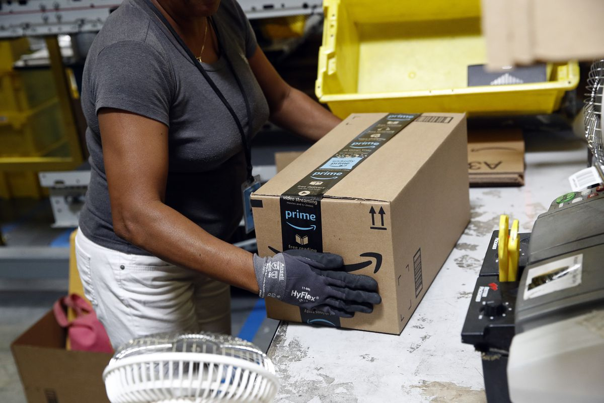 In this Aug. 3, 2017, file photo, Myrtice Harris applies tape to a package before shipment at an Amazon fulfillment center in Baltimore. Amazon's Prime Day starts July 16, 2018, and will be six hours longer than last year's and will launch new products.